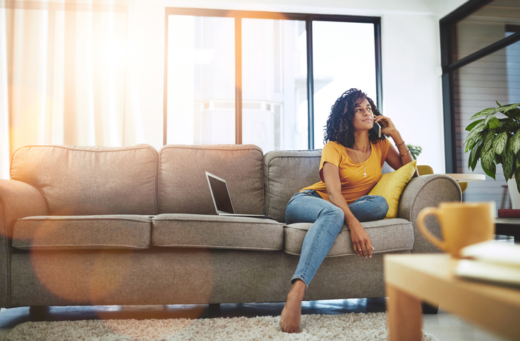 Woman using her cellphone while sitting on the couch.
